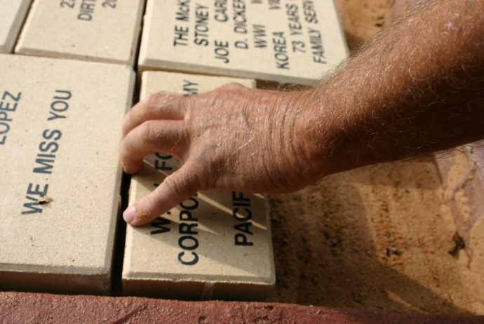 Bill Richter, 27th Civil Engineering Squadron, places a memorial brick at the Bataan Memorial. June 6 marked the one-year anniversary of the dedication of the memorial at Cannon Air Force Base. (U.S. Air Force photo by Airman Elliott Sprehe)